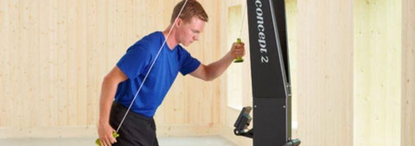 Mand i blå trøje der træner med skimaskine
